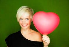 Love. Female couple love girl holding red heart as gift for boyfriend Stock Photos