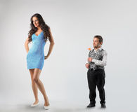 Love. Strange couple: dwarf paying court to tall woman Stock Photography