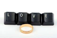 Love. Word formed by computer keyboard keys with wedding ring Stock Photo