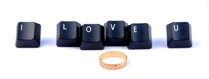 Love. Word formed by computer keyboard keys with wedding ring Stock Images