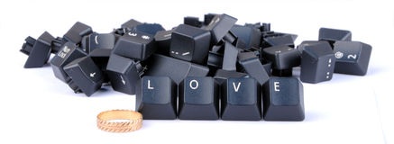Love. Word formed by computer keyboard keys with wedding ring Stock Photography