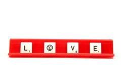Love. Scrabble pieces spelling the word LOVE on a red board Stock Images