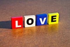 Love. Plastic blocks isolated on wood board background stock photos