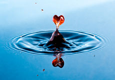 Love. Water-drop shaped as a figuratively heart symbolizing love. Isolated on a blue gradient