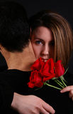 Love. A woman hugging her husband holding roses royalty free stock photography