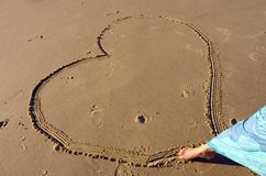 Love. Woman drawing heart on the sand Stock Photography