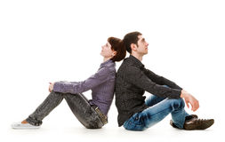 Love. Young woman and man sitting on the floor, back to back, isolated on white background Stock Photos
