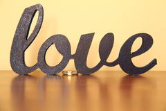 Love. Word love and engagement ring sitting on table Stock Photos
