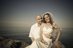 Love. A groom and bride on rock at beach Stock Image
