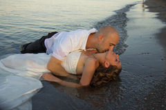 Love. A groom kissing brides neck on beach Royalty Free Stock Images