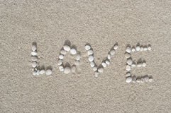 Love. Drawn word love with little stones on sand beach Royalty Free Stock Image