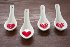 Only love. Four white porcelain spoons, red hearts on them, their tissue, a dark wooden table Royalty Free Stock Photos