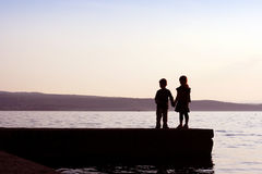 Love. Girl and boy holding hands by the sea - silhouette Royalty Free Stock Photo