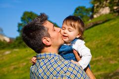 Love. Happy young men holding and kissing a 16 months old child royalty free stock photo