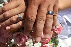 In Love. Two hands across each other showing off glinting wedding rings int he sun light Stock Photo
