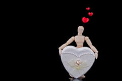 Love. A mannequin, who is in love, holding a big white heart with black background stock photography