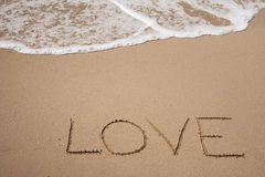 Love. Handwritting on the sand with seafoam and wave Stock Photo