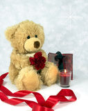 Love.... Cute fluffy teddy holding a red carnation and with red ribbon,candle and gift bag Stock Photos