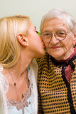 Love. A young woman kissing an older one  (focus on the elderly) - part of a series Stock Images