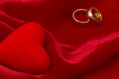 Love. Wedding rings and heart shape on red satin stock images