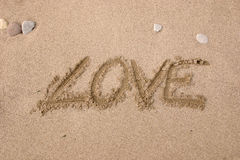 Love. Drawing on the sand - Love Stock Image