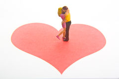 Love. Miniature figures embracing on a red heart Stock Photos