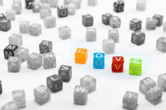 Love abstract. Isolated colorful small cubes scattered on white background. Stock Photos