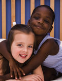 Love and Acceptance. A young African American child hugs a Caucasian girl Royalty Free Stock Photography
