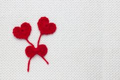 Love affair, love story. Two red crochet wool hearts and ribbon on white crochet background. The concept for 14 February, romantic. Valentine day. Festive royalty free stock photos