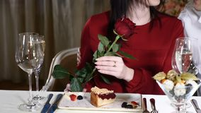 Love affairs. 14 February concept. Young attractive woman holding a red rose . Man scents. Young couple on date in. Restaurant stock video