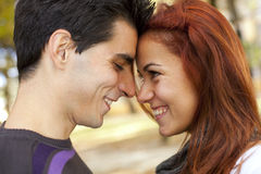Love and affection between a young couple. At the park in autumn season (selective focus with shallow DOF Royalty Free Stock Image