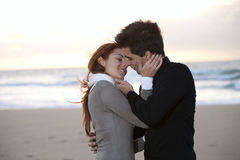 Love and affection between a young couple. At the beach in sunny day (selective focus with shallow DOF Stock Photos