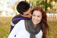 Love and affection between a young couple. At the park in autumn season (selective focus with shallow DOF Stock Photography