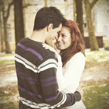 Love and affection between a young couple. At the park in autumn season (selective focus with shallow DOF Royalty Free Stock Photography