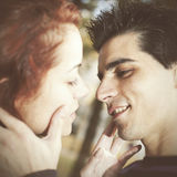 Love and affection between a young couple. At the park in autumn season (selective focus with shallow DOF Stock Photos