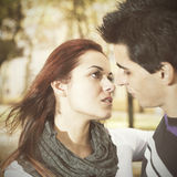 Love and affection between a young couple. At the park in autumn season (selective focus with shallow DOF Stock Image