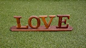 Love is in the air and on the green - Word LOVE lay on grass - W Stock Photos