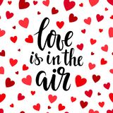 Love is in the air. Hand drawn brush pen lettering on pink glittering hearts background. design for holiday greeting card and invi. Tation of the wedding Stock Images