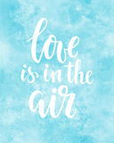 Love is in the air Hand drawn creative calligraphy and brush pen lettering on blue watercolour background. Royalty Free Stock Photography