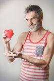 Love is in the air. Handsome old bearded man holding red heart in his hand Stock Photo