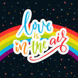 Love is in the air. Inspirational quote on rainbow parade flag at dark sky with stars. Gay pride saying for stickers, t Royalty Free Stock Photography