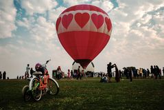 Love is in the Air. A love-themed hot air balloon gets ready for flight and a family`s bicycles are parked nearby. It`s Labor Day Lift Off in Colorado Springs Royalty Free Stock Images