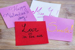 Love is in the air red note on a wooden background Royalty Free Stock Photography