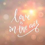 Love is in the air. Romantic quote calligraphy on morning sky with sun and light bokehs. Love is in the air. Romantic quote calligraphy on morning sky with sun Royalty Free Stock Image