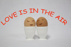 Love is in the air. Two painted egs like faces of a girl and a guy on the white background Stock Photo
