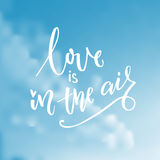 Love is in the air. Typography on blue sky with clouds. Valentine`s day card vector design with modern calligraphy.  Stock Images