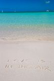 Love is in the air written on tropical beach white Royalty Free Stock Images