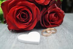 Love is all around. A loveletter from your valentine, red roses and the wedding ring as an external sign of inner connectedness Stock Photos