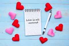 LOVE IS ALL AROUND word on note book and pen with red and pink heart shape decoration on blue wooden table background. Love, royalty free stock photo
