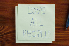 Love all people handwritten on a note Stock Photo